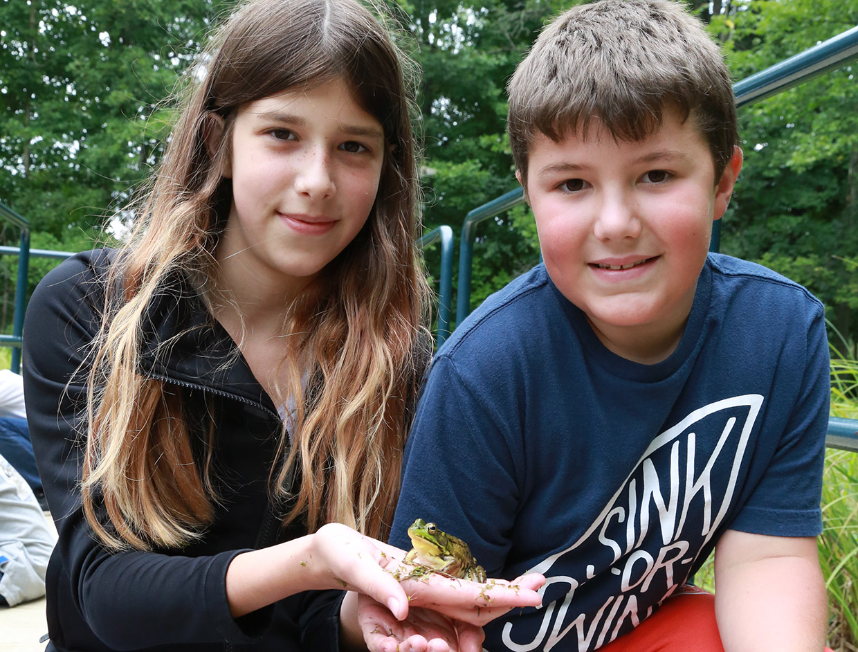 girl holds small frog at Kortright outdoor adventure camp