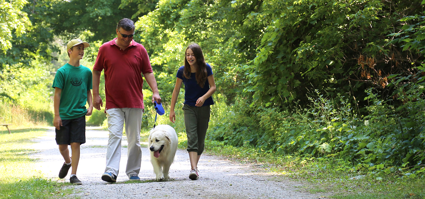 family taking dog for a walk on trail at Kortright Centre for Conservation