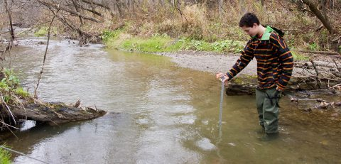 high school student takes stream flow measurement at Kortright Centre