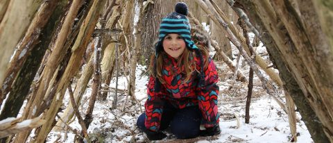 young girl sits inside forest shelter