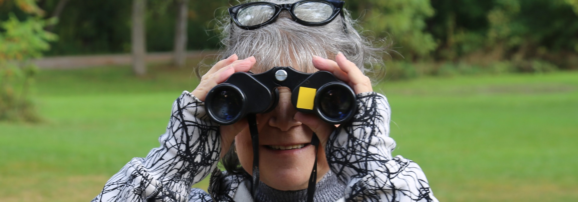 woman uses binoculars to birdwatch