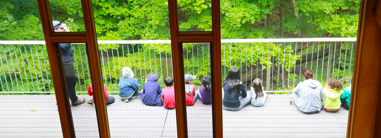 children sit on deck at Kortright Visitor Centre
