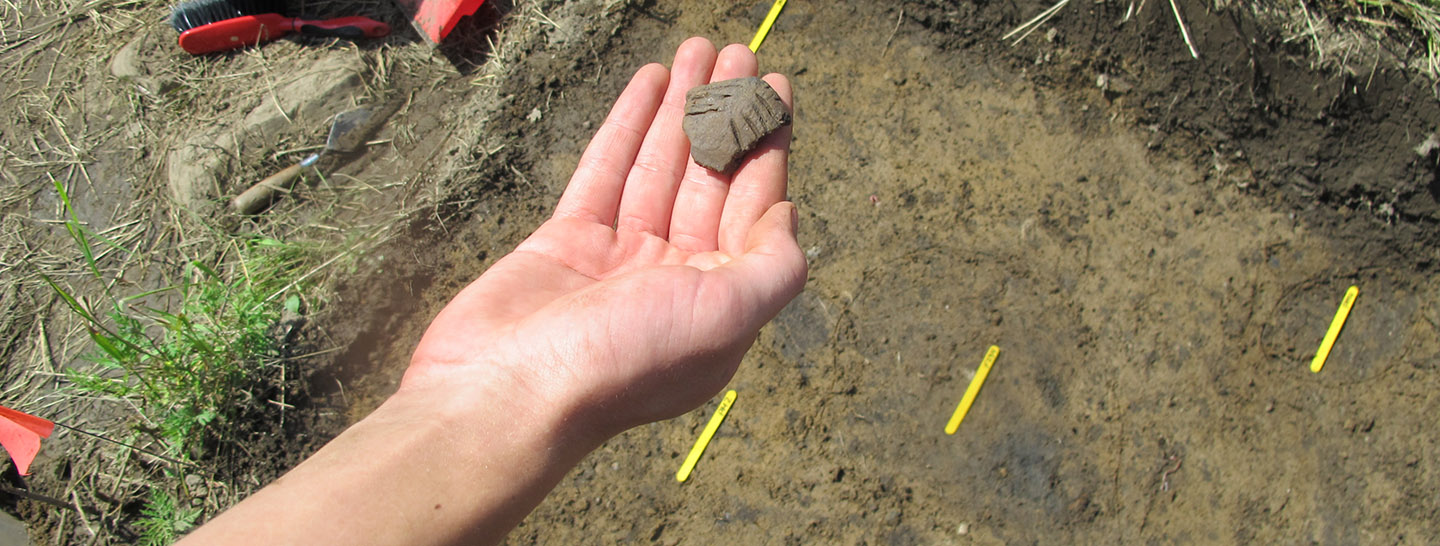 student holds artifact at archaeological dig site