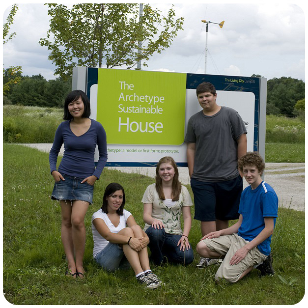 students pose with Archetype Sustainable House sign