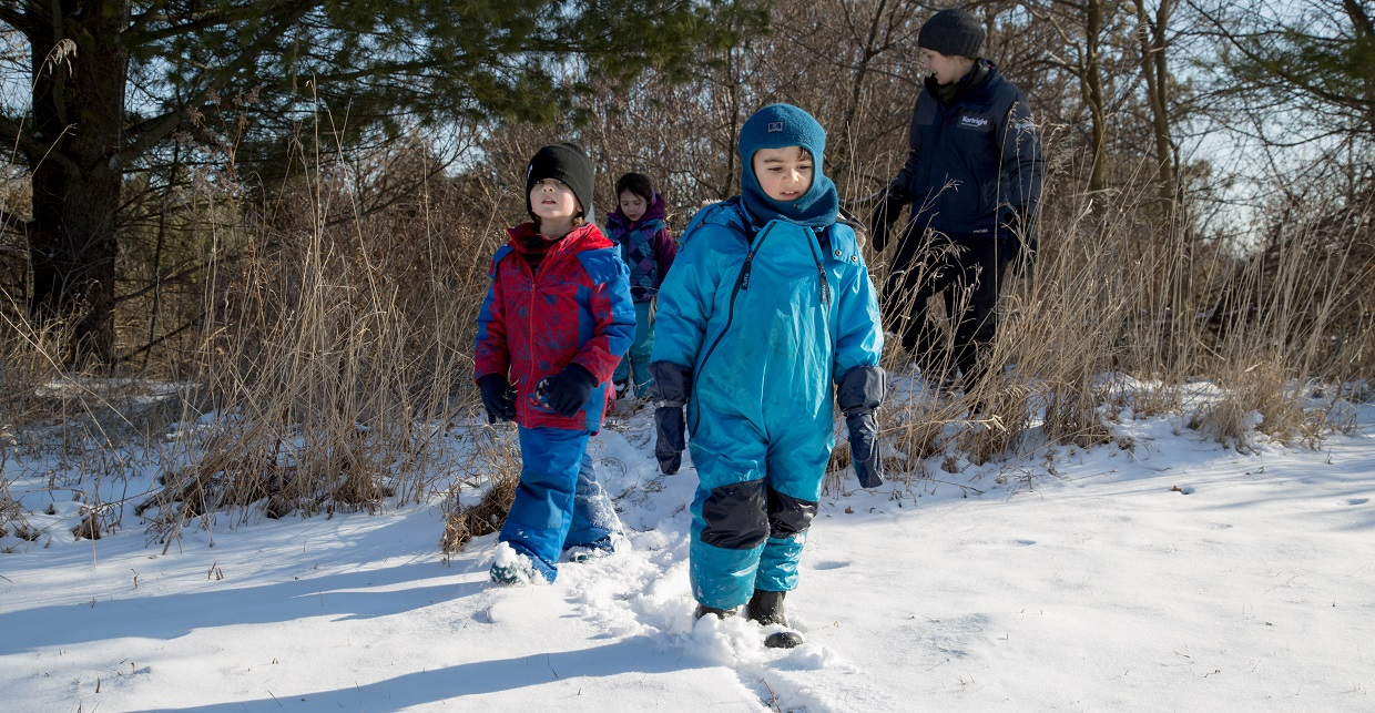 children and teacher explore Kortright Centre trail in winter