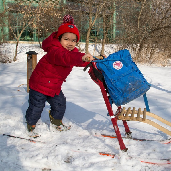 child plays with sled at Kortright Centre Family Day open house