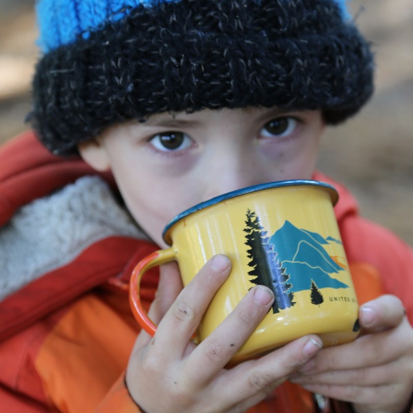 child drinking hot chocolate from mug