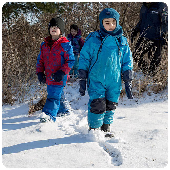 children hike through snow at Kortright Centre for Conservation