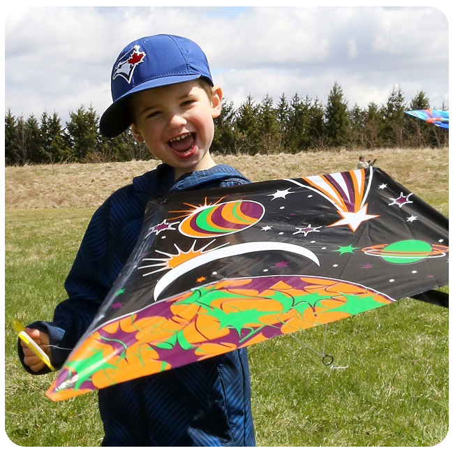 young boy holding kite in field at Kortright Centre