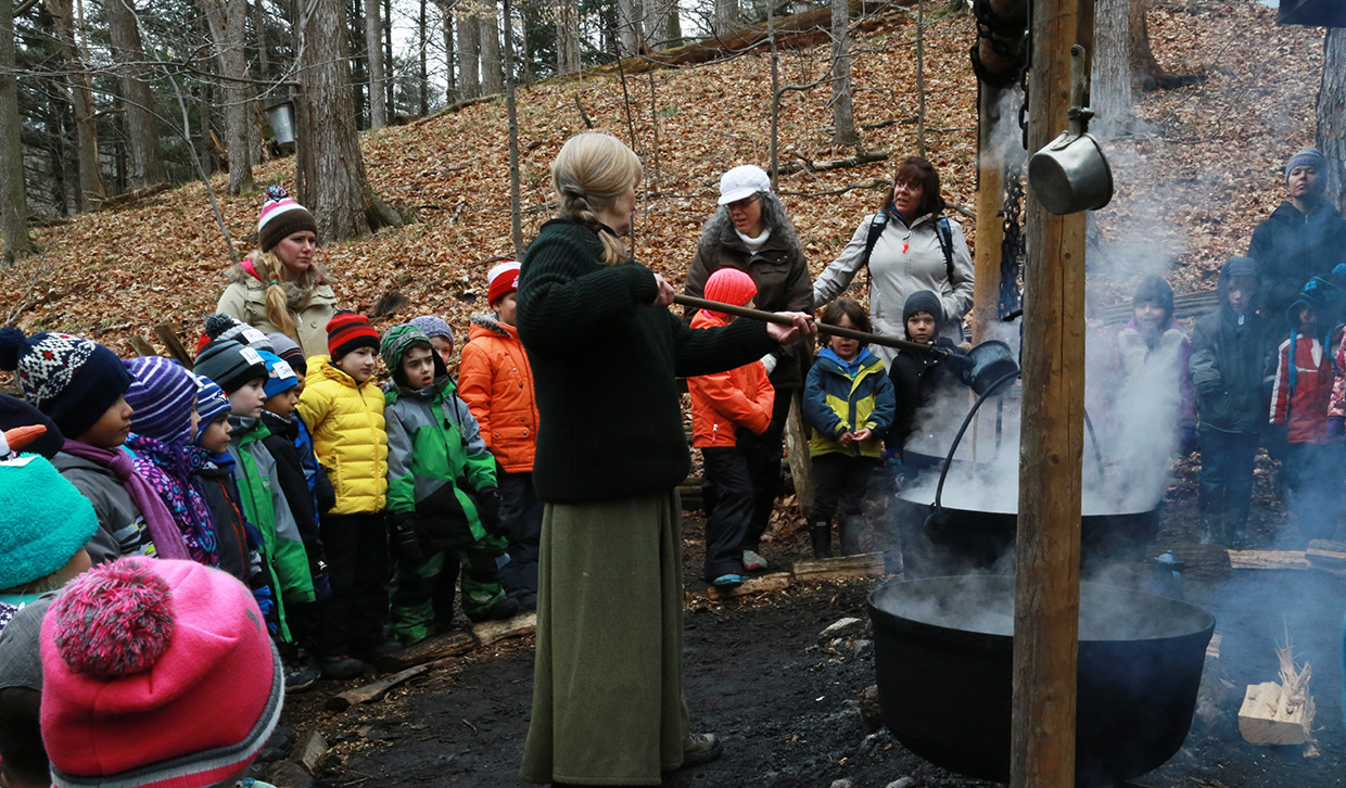 interpreter demonstrates traditional process of making maple syrup at Kortright Centre