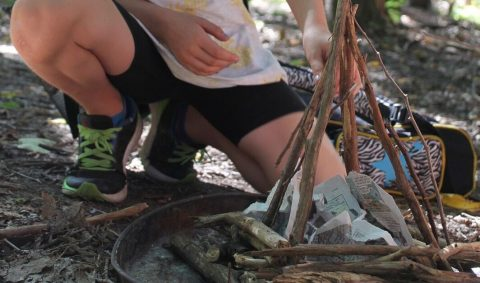 girl learns to build fire at Kortright summer survival skills day camp