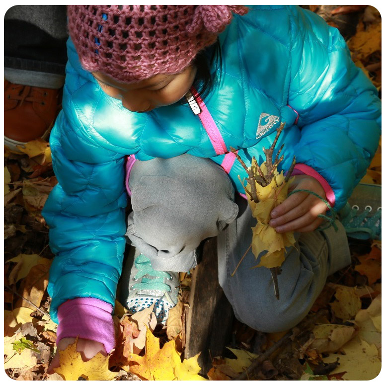 young girl gathers leaves at Kortright Nature School