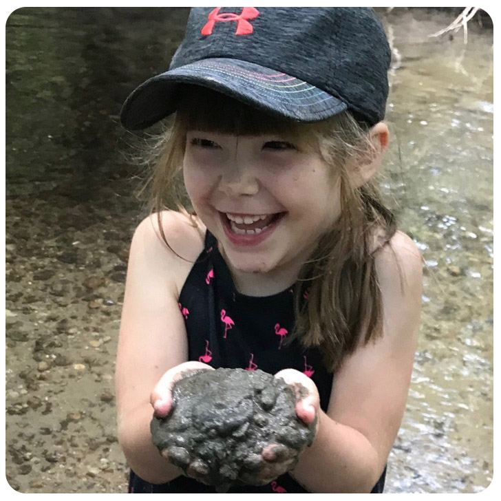 girl plays with mud at Kortright Centre summer camp
