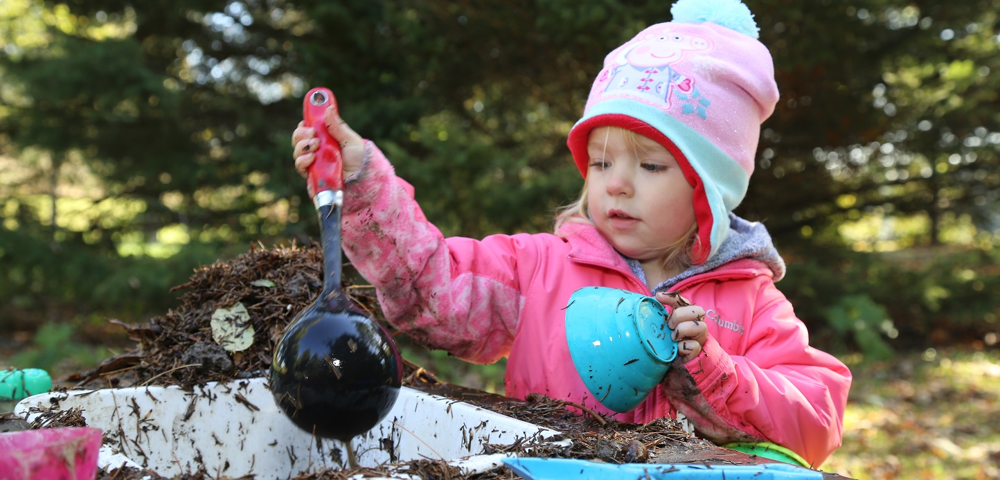 child playing in mud kitchen at Kortright nature school