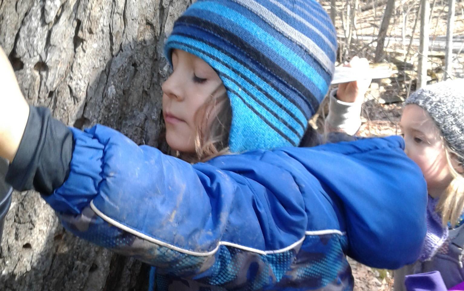child hugs tree