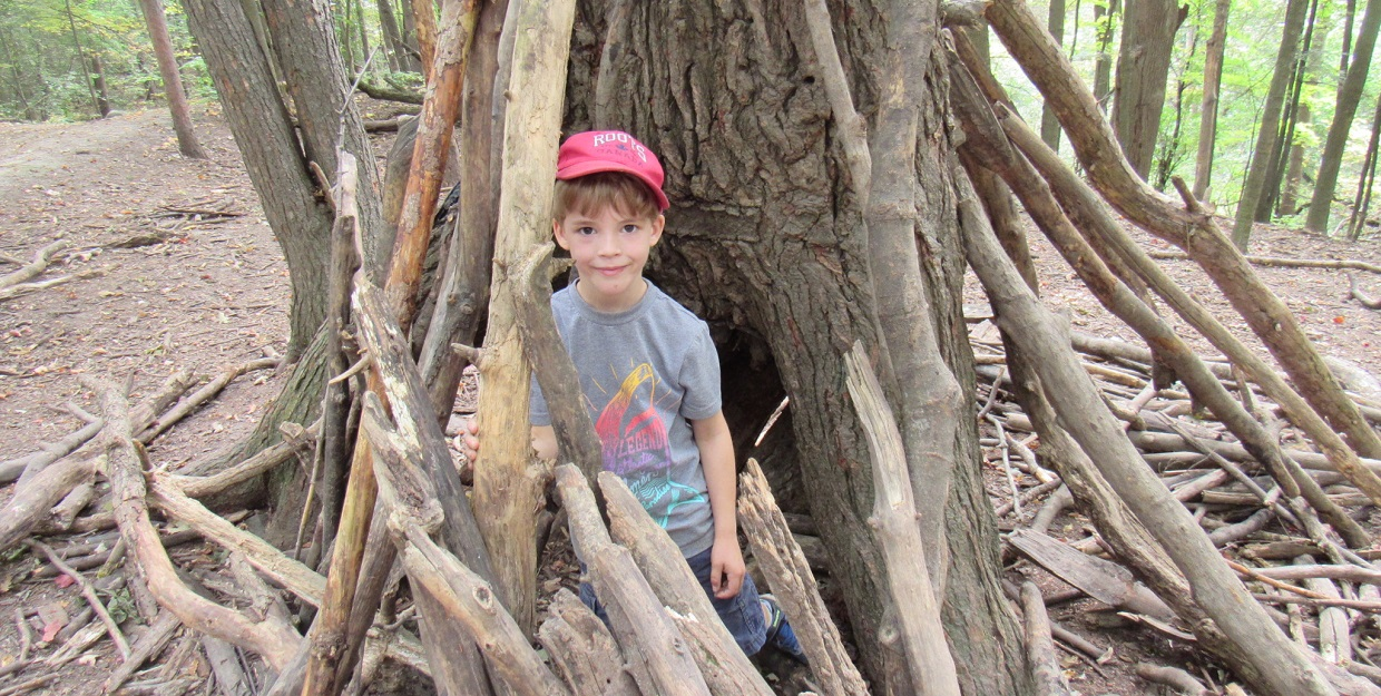 young boy builds a shelter of sticks and logs