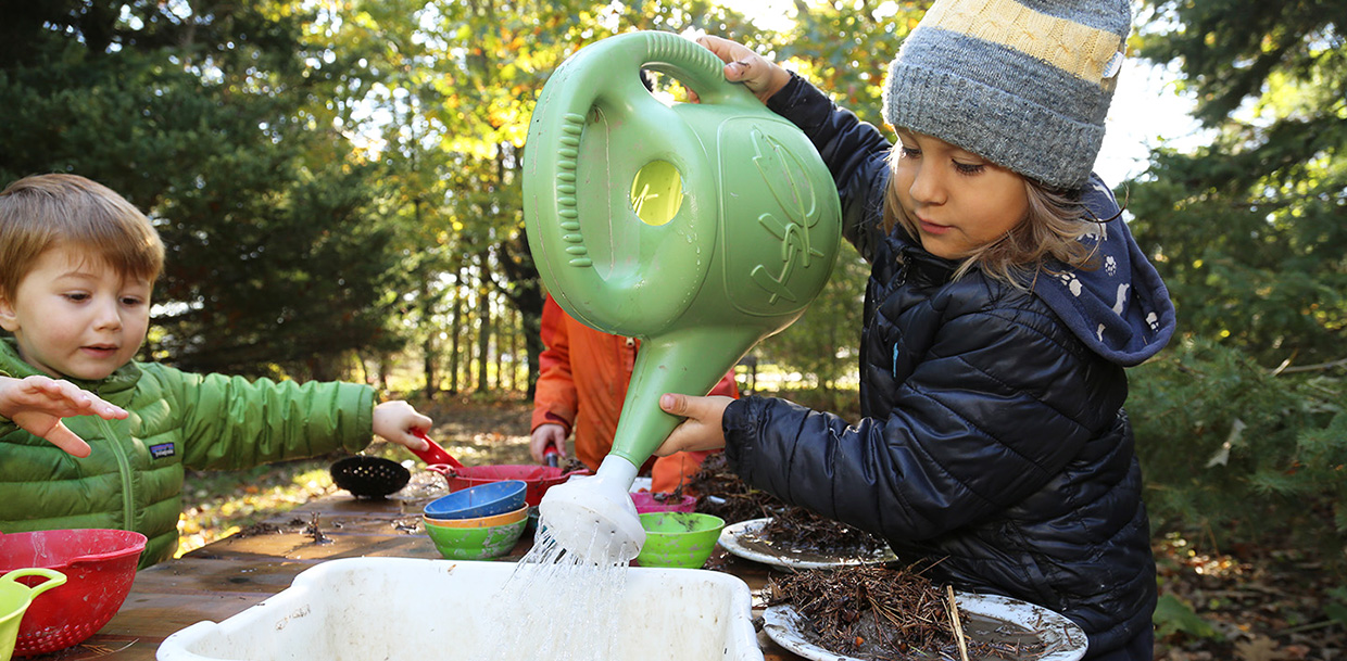 children play in mud kitchen at Kortright Centre Nature School