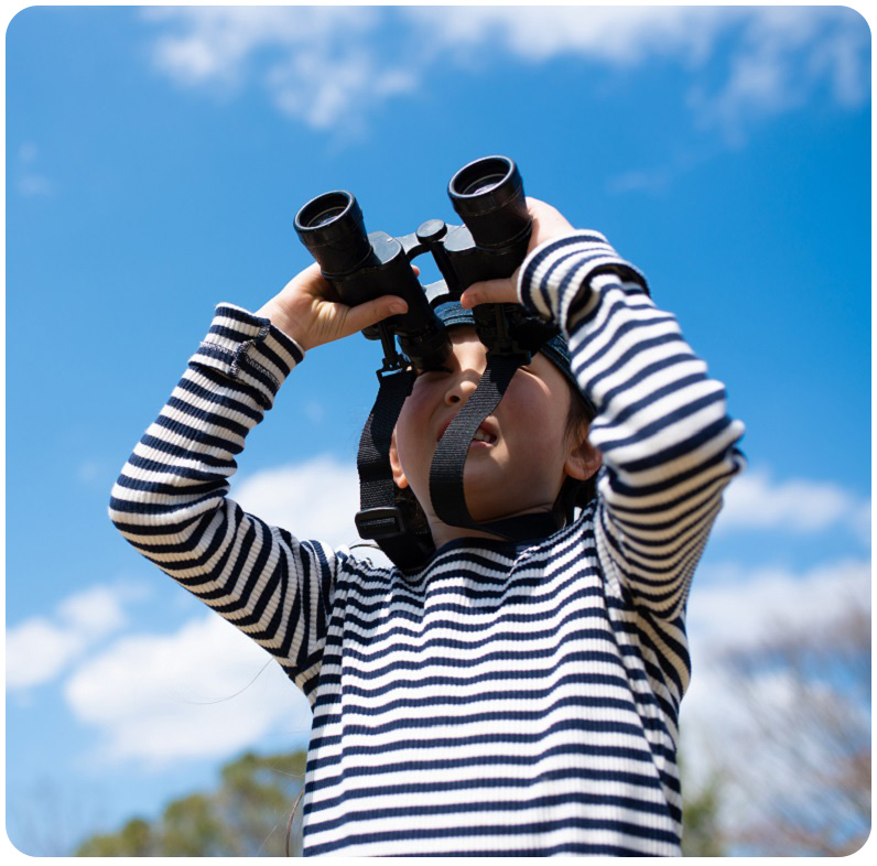 boy uses binoculars for birdwatching at Kortright Centre