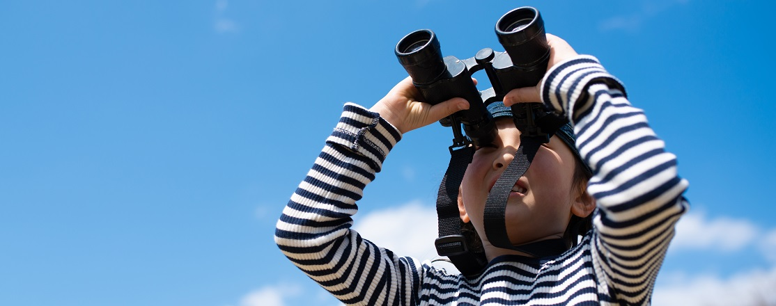 boy birdwatching with binoculars