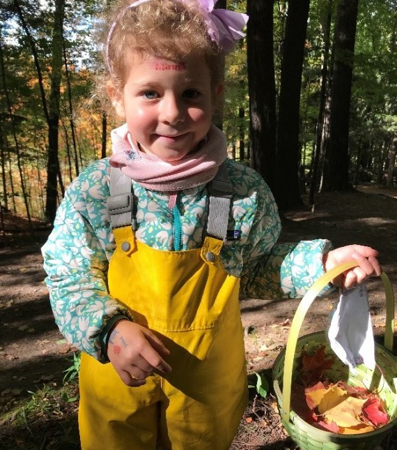 student at The Nature School uses a basket to collect colourful fall leaves