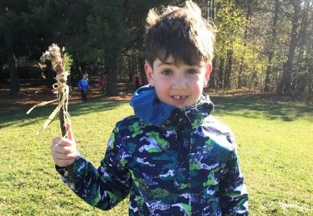 student at The Nature School at Kortright Centre proudly holds up a stick