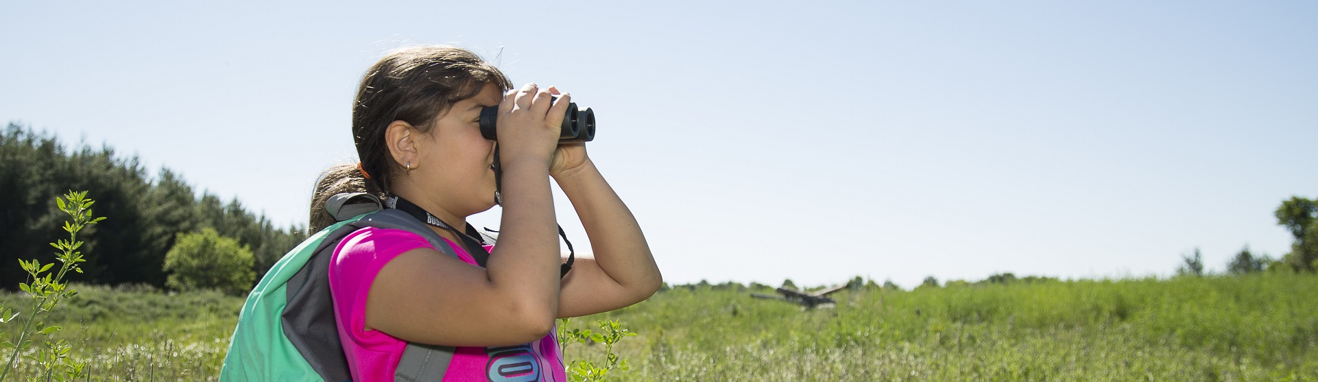 young visitor to Kortright Centre uses binoculars to look for birds