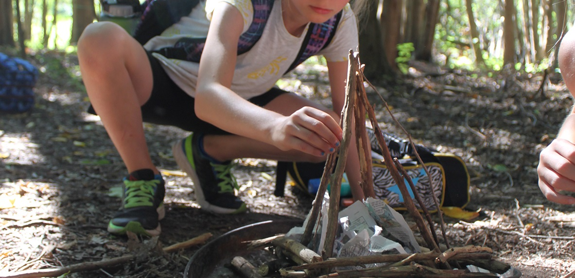young visitor to Kortright Centre learns to build a fire as part of the wilderness survival skills program