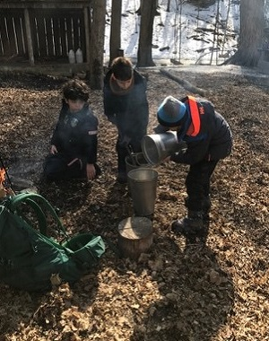 students at The Nature School pour sap into a kettle over a fire to make maple syrup