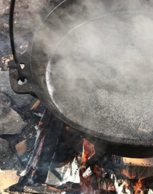 kettle filled with sap boils over a fire